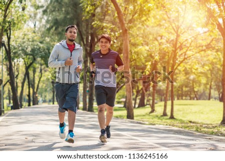 two sportsmen jogging in park in the morning #1136245166
