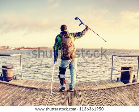 Man with a crutches on mole pier. Tourist with broken leg on crutches. Traveler with hurt leg in bandages. Full length of man with broken leg. #1136361950