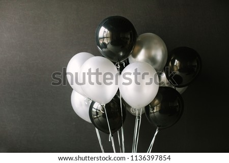 Black and white balloons on a dark black background. Celebration concept / White and black balloons on a dark black background for a holiday, birthday or other holiday. Photo for posters or postcards.