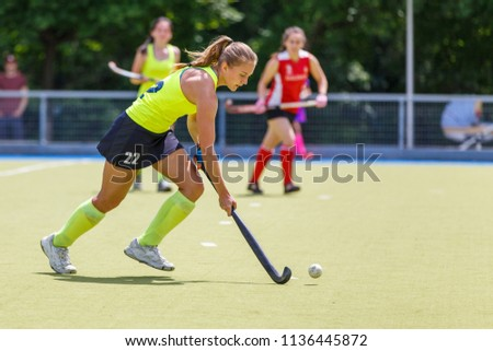 Young hockey player woman with ball in attack playing field hockey game #1136445872
