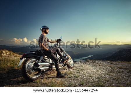 Biker leaning on a motorcycle enjoying the view #1136447294