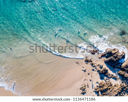 The Pass at Byron Bay from an aerial view with blue water Royalty-Free Stock Photo #1136471186