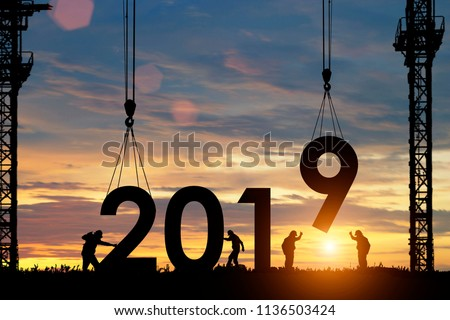 Silhouette staff works as a team to prepare to welcome the new year 2019. Royalty-Free Stock Photo #1136503424