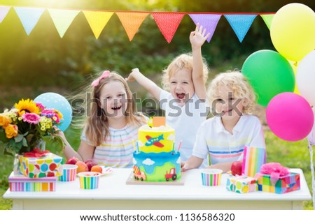 Children blow candles on birthday cake. Kids party decoration and food. Boy and girl celebrating birthday of little brother. Transport and car kid event theme. Child with presents and sweets. #1136586320