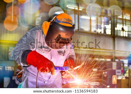 Industry welder worker with protective equipment welding pipe system and process success, light sparks, bokeh  #1136594183