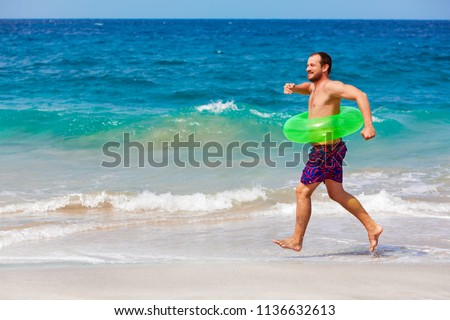 Happy bearded hipster in inflatable ring have fun on beach walk. Funny man run along sea surf and jump by water pool. Family travel lifestyle, swimming activities. Summer vacation on tropical island.