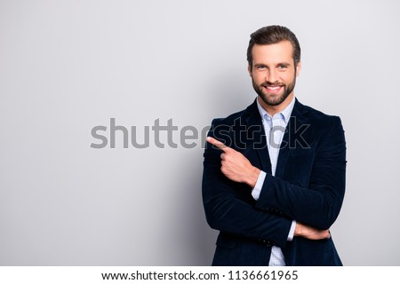 Portrait of cheerful excited joyful satisfied handsome attractive fashionable macho guy dressed in formal outfit dark velvet pointing on empty blank copyspace isolated on gray background copy-space #1136661965