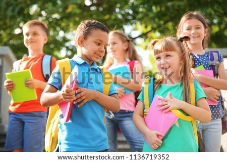 Cute little children with backpacks and notebooks outdoors. Elementary school #1136719352