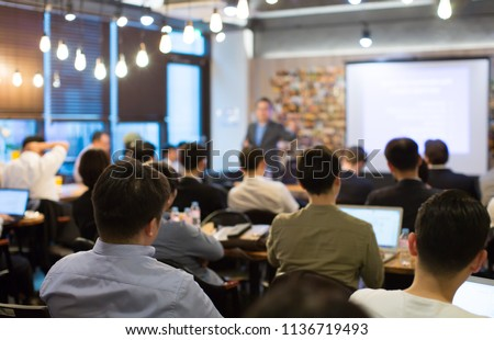 Audience Listens to Lecturer at a Conference Meeting Seminar Training. Group of People Hear Presenter Give Speech . Corporate Manager Speaker Gives Business Technology and Economic Forecast. #1136719493