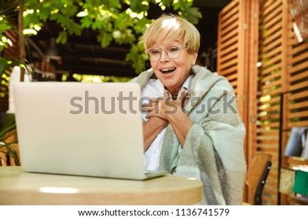 Excited mature woman wrapped in blanket sitting at a cafe with laptop computer #1136741579