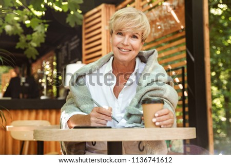 Happy mature woman writing in a notebook while sitting at a cafe and drinking coffee #1136741612