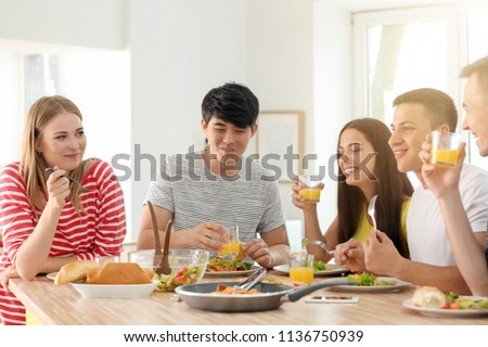 Friends eating at table in kitchen #1136750939