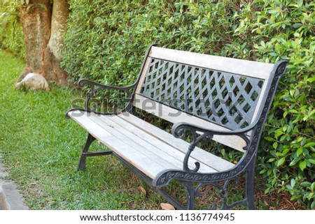 Wooden chairs placed in a garden with trees in the background with sunlight. #1136774945
