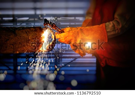 Close-up view of Industrial Worker at the factory welding . Welded man priority Choose a skilled welder in welding . concept for construction and safety in worked . #1136792510