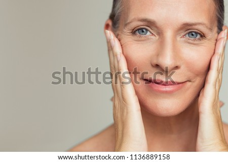 Portrait of beautiful senior woman touching her perfect skin and looking at camera. Closeup face of mature woman with wrinkles massaging face isolated over grey background. Aging process concept. #1136889158