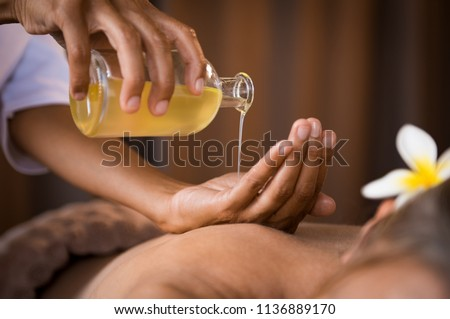 Closeup of masseur hands pouring aroma oil on woman back. Masseuse prepare to do oriental spa procedure for relaxing treatment. Therapist doing aromatherapy oil massage on woman body. #1136889170