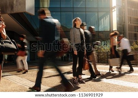 Woman standing amidst a busy office going crowd hooked to their mobile phones. Businesswoman holding her hand bag standing still on a busy street with people walking past her using mobile phones. #1136901929