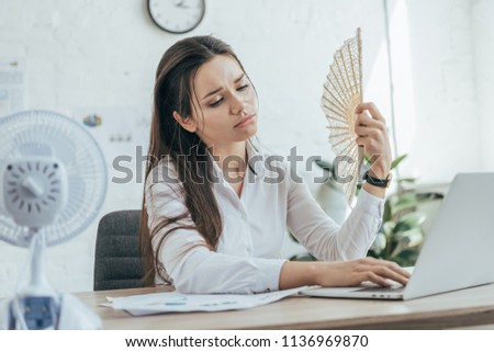 exhausted businesswoman using laptop while conditioning air with electric fan and hand fan in office #1136969870