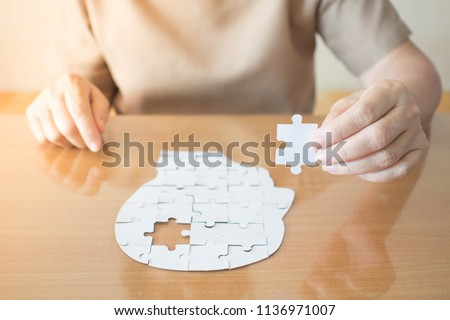Elderly woman hands holding missing white jigsaw puzzle piece down into the place as a human head brain shape. Creative idea for memory loss, dementia, Alzheimer's disease and mental health concept. #1136971007