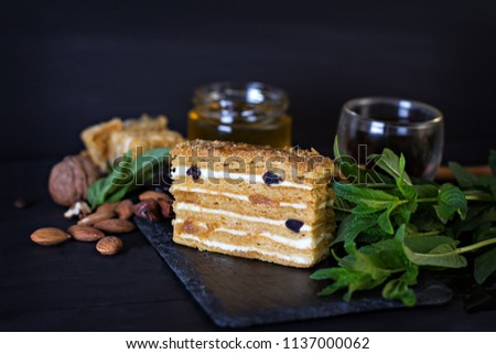 Cake with cream and dried fruits. The Medovik. Cake and a cup of espresso. Honey cake with dried fruits (dried apricots, prunes and nuts) and espresso on a dark background. Dark photo.