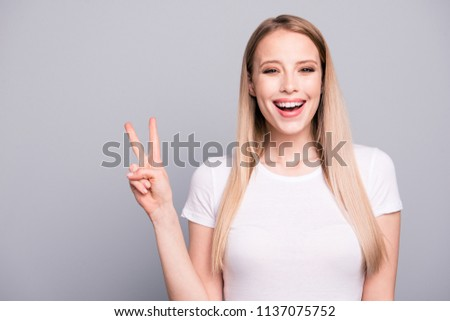 Portrait of young caucasian blonde charming attractive smiling girl showing v-sign gesture. Isolated over grey background, copy space #1137075752