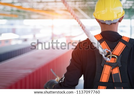 Construction worker wearing safety harness and safety line working at high place #1137097760