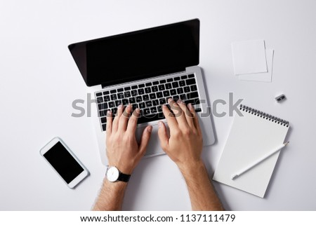 cropped shot of man typing with laptop at workplace on white surface for mockup #1137111479
