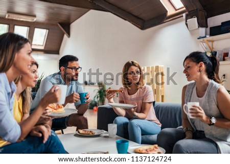 Group of adult friends talking and eating pizza at home. #1137124724