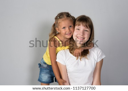 Two girls sisters teenager and child on gray background #1137127700