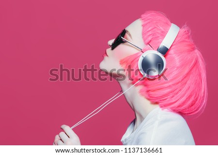 Trendy girl with pink hair wearing sunglasses enjoys the music on headphones. Pink background. Youth style, leisure. #1137136661