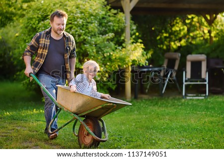 Happy little boy having fun in a wheelbarrow pushing by dad in domestic garden on warm sunny day. Active outdoors games for kids in summer. #1137149051