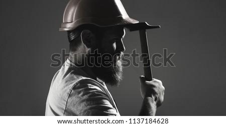 Hammer hammering. Builder in helmet, hammer, handyman, builders in hardhat. Handyman services. industry, builder man. Bearded man worker with beard, building helmet, hard hat. Black and white. #1137184628