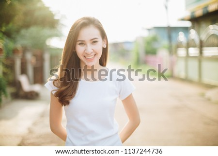 A happy young woman enjoying the autumn on the street #1137244736