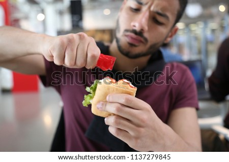 Hungry man sitting in a restaurant, holding a ketchup packet adding it to his sandwich Royalty-Free Stock Photo #1137279845