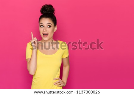 Happy beautiful young woman in yellow top is pointing up, looking away and talking. Waist up studio shot on pink background. Royalty-Free Stock Photo #1137300026