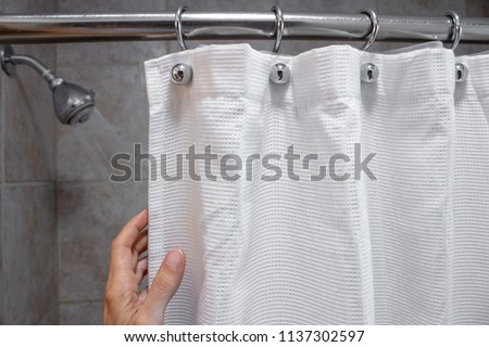a hand pulling back a shower curtain revealing a shower head with water on horizontal shot #1137302597