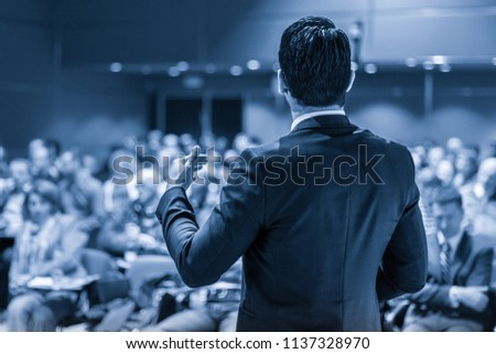 Speaker giving a talk on corporate business conference. Unrecognizable people in audience at conference hall. Business and Entrepreneurship event. Blue toned grayscale image. #1137328970