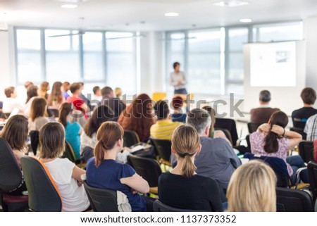 Business and entrepreneurship symposium. Speaker giving a talk at business meeting. Audience in conference hall. Rear view of unrecognized participant in audience. #1137373352