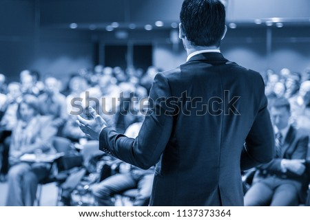 Speaker giving a talk on corporate business conference. Unrecognizable people in audience at conference hall. Business and Entrepreneurship event. Blue toned grayscale image. #1137373364