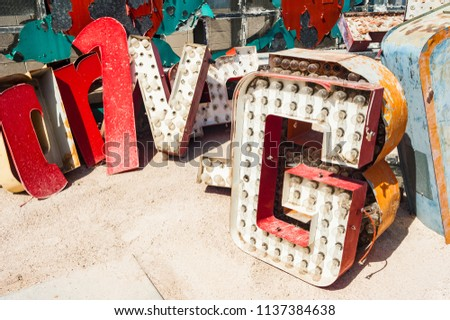Close-up details of old signs with vintage light bulbs, metal letters and peeling paint. Colorful abstract signage, painted details and complex textures, copy space.