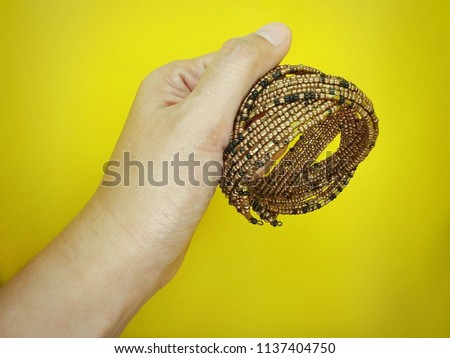 Closeup female hand with jewelry and accessories. Isolated on yellow background.(selected focus) #1137404750
