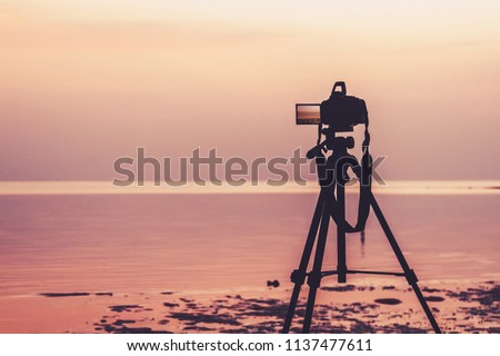 Dslr digital professional camera stand on tripod photographing sea, twilight sky and cloud landscape. nature background.image,picture on screen. dslr camera shoting nature landscape.camera on a tripod