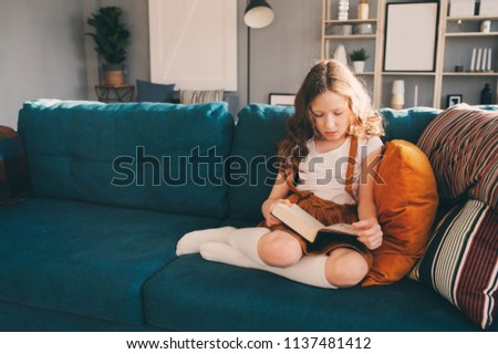 concentrated child girl reading interesting book at home #1137481412