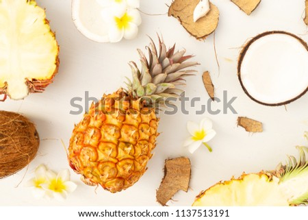 Summer flat lay scene with tropical fruits pineapples and coconuts on light gray wooden background #1137513191
