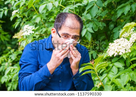 a middle-aged man near a tree with flowers, he is allergic to pollen #1137590330