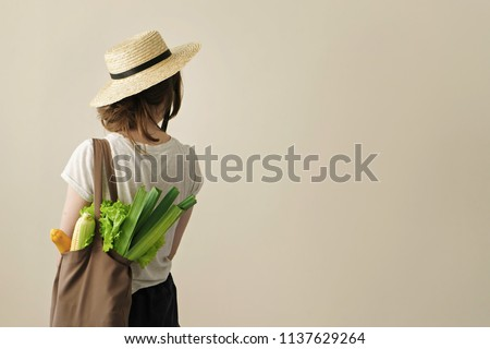 young woman holding textile glocery bag with vegetables  #1137629264