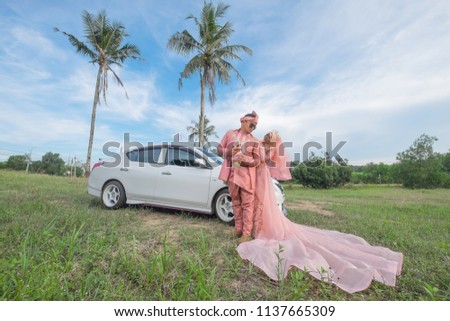 Muadzam Shah, Malaysia -  April 28th, 2018 : Outdoor shooting for happy Malay wedding couple .The brides and grooms wearing pink Malay traditional cloth with beautiful background #1137665309