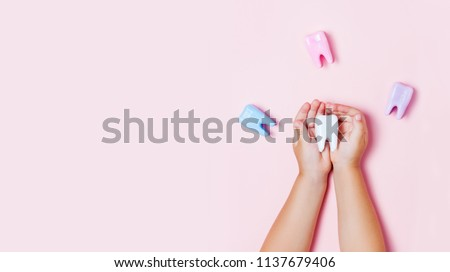 Child's hands holding big tooth and toothbrush on pink backgroubd. Healty care teeth concept. Top view, flat lay. Copy space for your text. Royalty-Free Stock Photo #1137679406