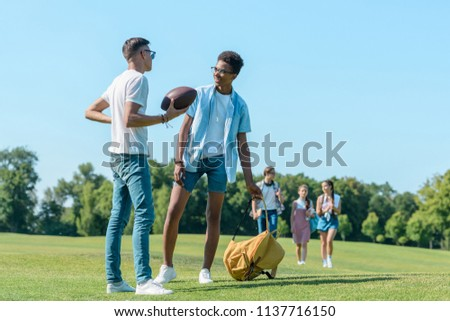 multiethnic boys playing with rugby ball while classmates walking behind in park  #1137716150