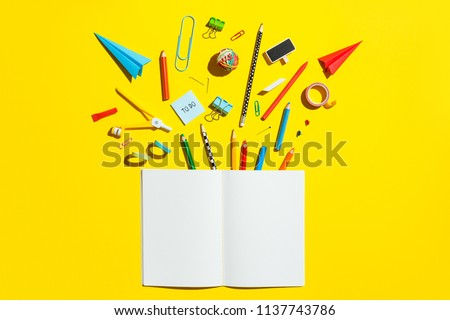 School notebook and stationery over yellow desk. Back to school abstract background. Royalty-Free Stock Photo #1137743786